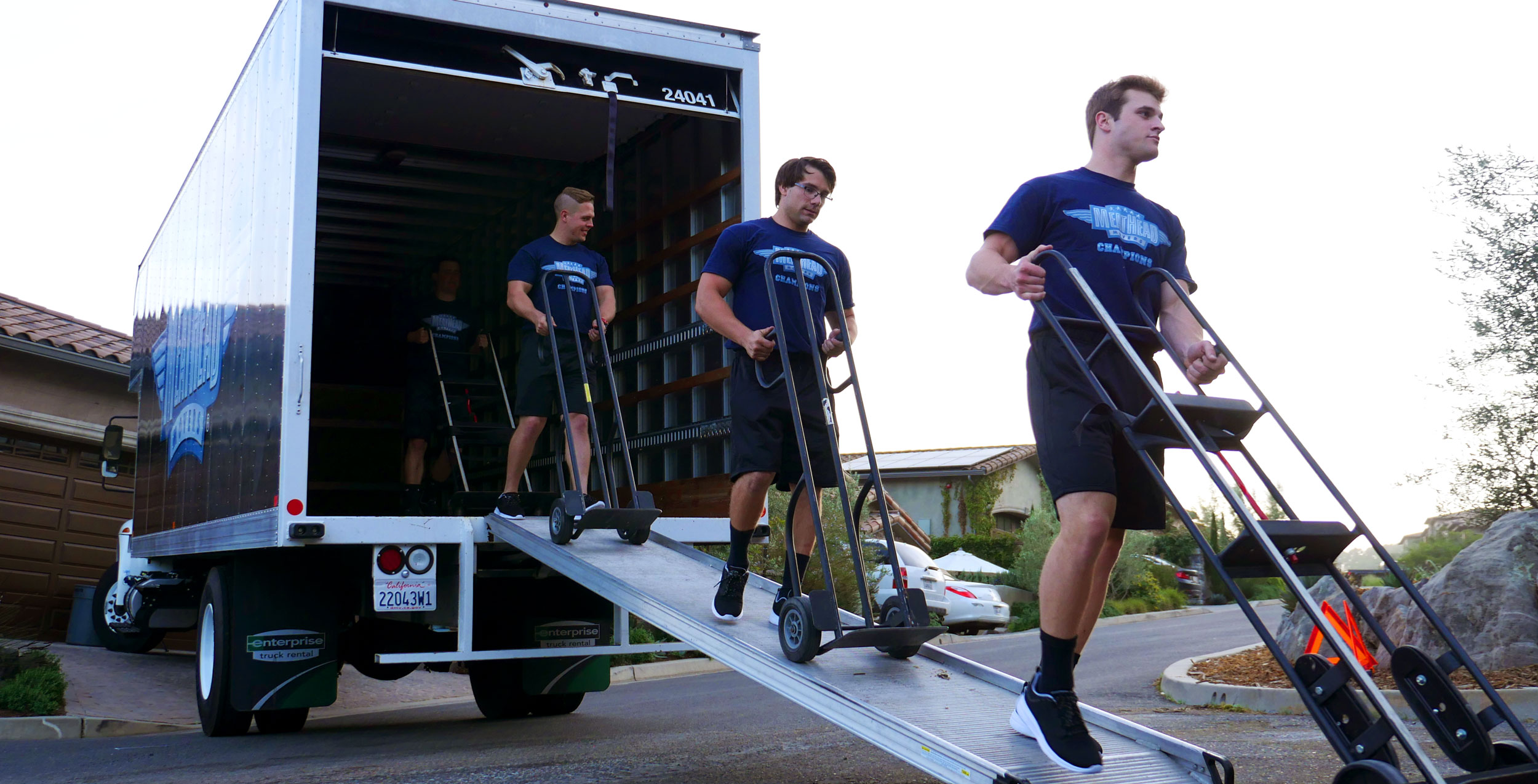 Meathead Movers walking out of a truck after loading it with boxes.