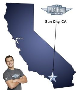 An arrow pointing to the city of Sun City on a map of California with an athletic Meathead Mover standing happily next to the state.