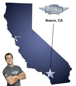 An arrow pointing to the city of Nuevo on a map of California with an athletic Meathead Mover standing happily next to the state.