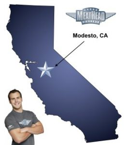 An arrow pointing to the city of Modesto on a map of California with an athletic Meathead Mover standing happily next to the state.