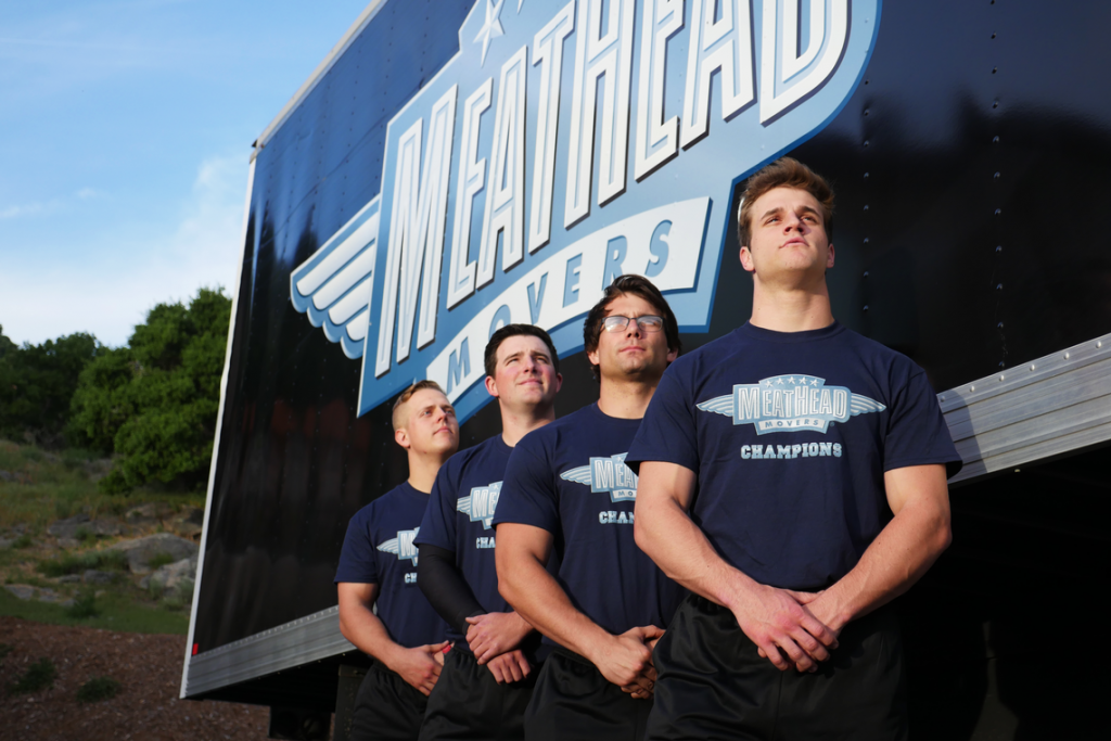 Four Meathead Movers proudly standing next to a moving truck.