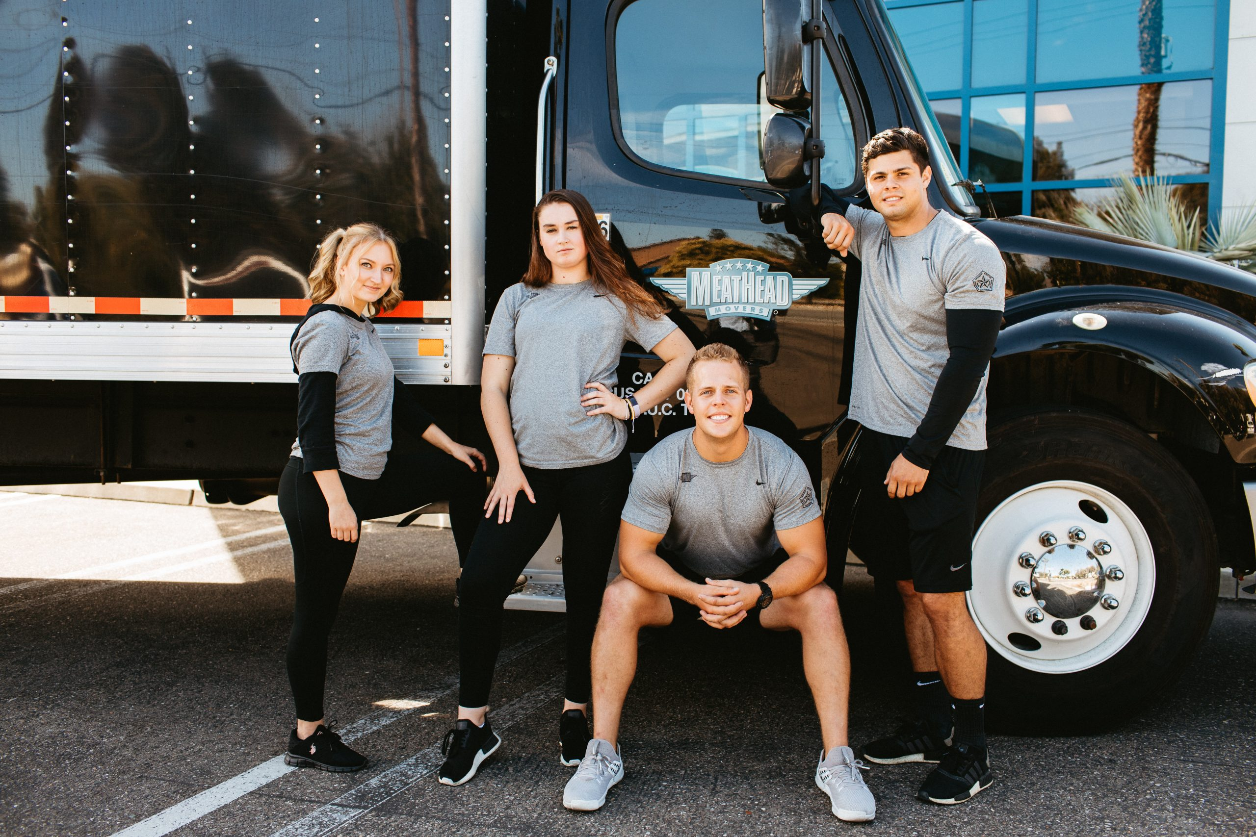 Student athlete movers standing by a moving truck.