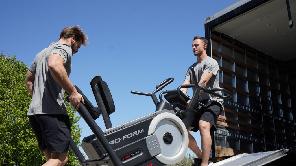 Two Meathead Movers lifting an elliptical machine into a moving truck.