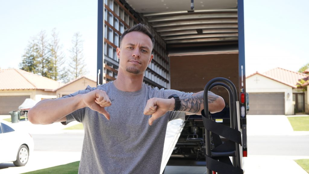 A Meathead Mover standing near the back of a moving truck with his thumbs pointed down.